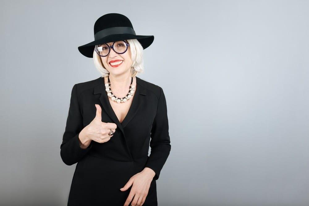 Femme senior en noir chapeau pouce en l'air by Mademoiselle M