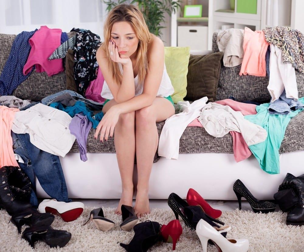 Femme triste entourée de vêtements sur canapé by Mademoiselle M