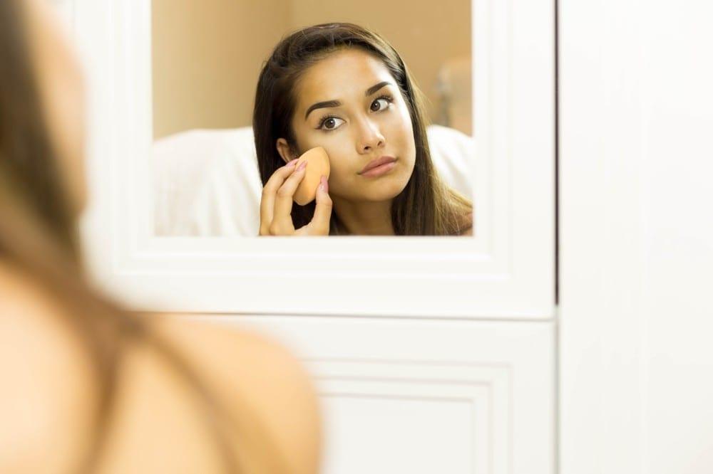 Jeune femme appliquant fond de teint au miroir by Mademoiselle M